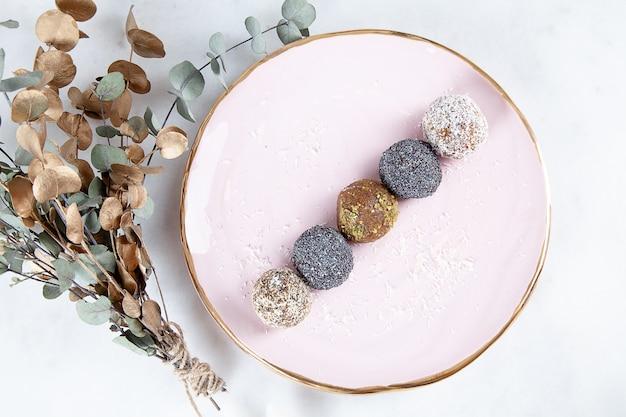 Крупным планом вид на другой набор сырых, здоровых, без сахара, веганский конфеты. сладкие пироги для диетического меню. безглютеновые сладости. сырые конфеты. энергетические шарики на розовой тарелке. плоская планировка