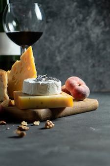 赤ワインとチーズ。まな板の上のナッツ、ラベンダー、イチジクの桃とさまざまな種類のチーズ。ロマンチックなディナー。デザインのスペースをコピーします。暗い背景。ソフトフォーカス