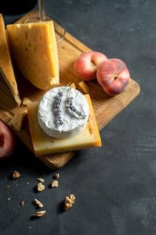 Вид сверху на сыр на темном фоне. камамбер, сыр со специями, голландский сыр на разделочной доске с орехами, лавандой и инжирным персиком. копировать пространство плоская кладка еды. выборочный, мягкий фокус. темный угрюмый