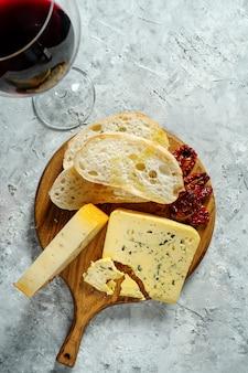木製のまな板にチーズの種類。チャバタとサンドライトマトと灰色の背景にワインのグラスとブルーチーズ。イタリア料理のディナー。コピースペース。ソフトフォーカス、トップビュー