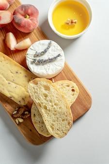 木製のまな板にさまざまな種類のチーズの平面図です。イチジクの桃、蜂蜜、チャバタ、ナッツのチーズ、赤ワインのグラス。スタイリッシュな食品フラットは灰色の背景に横たわっていた。コピースペース。ソフトフォーカス
