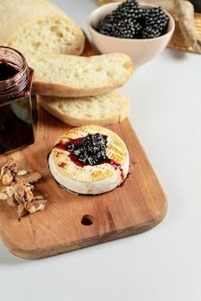 灰色の背景にブラックベリージャム、ナッツ、チアバッタのグリルカマンベールのビューを閉じます。コピースペース。チーズ。ランチにおいしい料理。ソフトフォーカス。ワインの食べ物