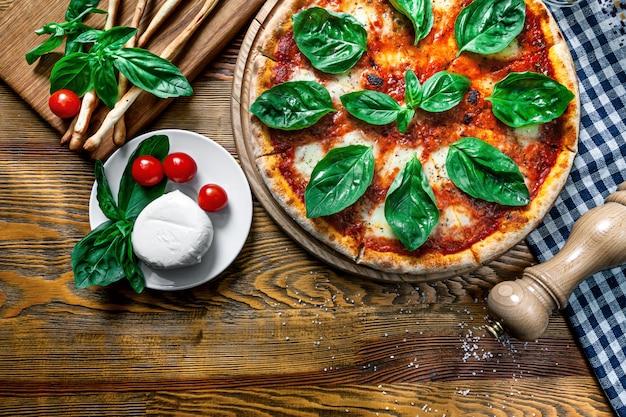 木製のテーブルに新鮮な自家製マルガリータピザの平面図です。デザインのコピースペースを持つ平面図食品。食材を使ったピザ:チェリートマト、モザレラ。イタリア料理