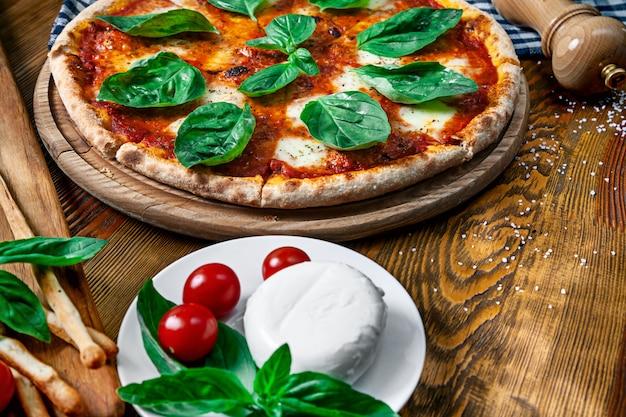 木製の背景の成分と新鮮な自家製マルガリータピザのビューを閉じます。モッツァレラ、バジル、チェリートマト。デザインのスペースをコピーします。メニューの写真、イタリア料理