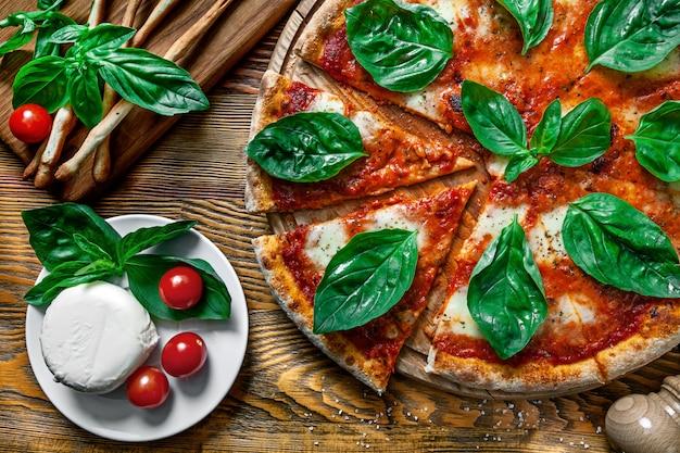 木製の背景の成分と新鮮な自家製マルガリータピザの平面図です。モッツァレラ、バジル、チェリートマト。デザインのスペースをコピーします。メニューの写真、イタリア料理