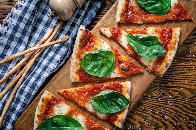 木製のまな板の背景にスライスしたマルガリータピザの平面図です。デザインのコピースペースの刈り取らピザ。メニューの写真、イタリア料理