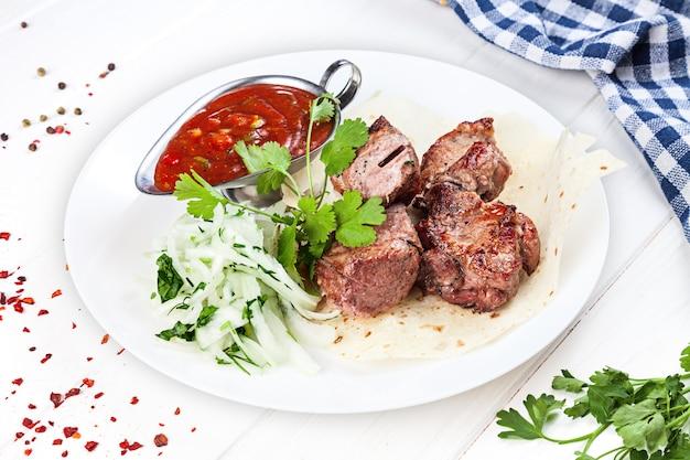 グリルポークで調理された役立った上のビューを閉じます。シャシリクまたはバーベキュー肉のピタ。シシカバブ、伝統的なジョージア料理。デザインのコピースペース