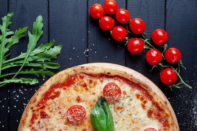 ピザマルガリータのトップビュー。黒い木製の背景にフラットピザ、トマト、ルッコラと食品を置きます。イタリアの自家製ピザ。イタリア料理。コピースペース。上からの眺め。ビーガンフード