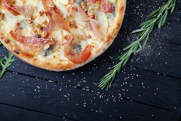 Пицца с хамоном, сыром горгонзола и сыром пармезан, орехами и грушей. вид сверху. свежая домашняя итальянская пицца. продовольственный фон. пицца с мясом и сыром на темном деревянном фоне