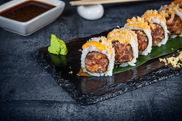 Крупным планом вид на набор суши ролл. пряный ролл с тунцом и икрой подается на черном камне на темном фоне. японская кухня. копировать пространство подается суши для меню. здоровая еда, морепродукты