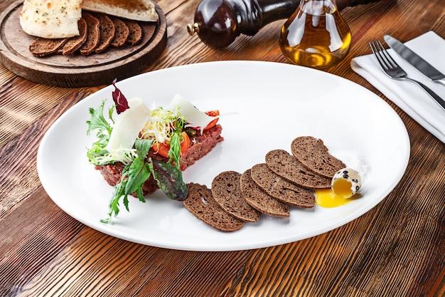 パン、卵、白い皿にマイクログリーンの新鮮なタルタルビーフのビューを閉じます。コピースペースを持つ木製の背景に自家製タルタル仔牛。メニューやレシピの料理を提供しています。イタリア料理の前菜