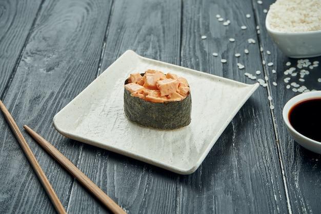 古典的な日本のロール寿司-黒い木製の背景に白いセラミックプレートにチキンとスパイシーなホワイトソースの軍艦。閉じる