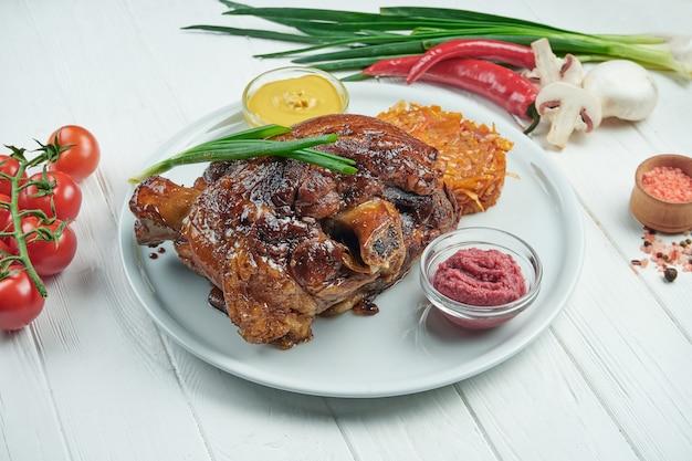 Аппетитная запеченная свиная рулька в пиве и мёде с жареной капустой и горчицей. традиционные немецкие и чешские пивные закуски. белый деревянный фон. рулька