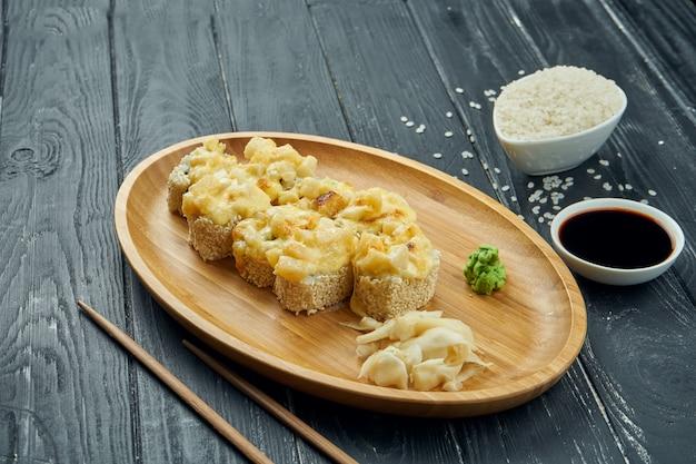 古典的な日本のロール寿司-黒の木製の背景に竹皿にクリームチーズ、スパイシーソース、チキンのロールパン