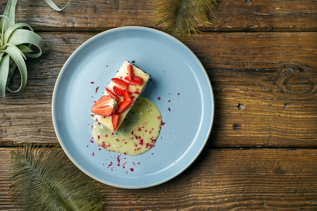 Здоровый десерт - творожная запеканка с маком и клубникой в тарелке на деревянном