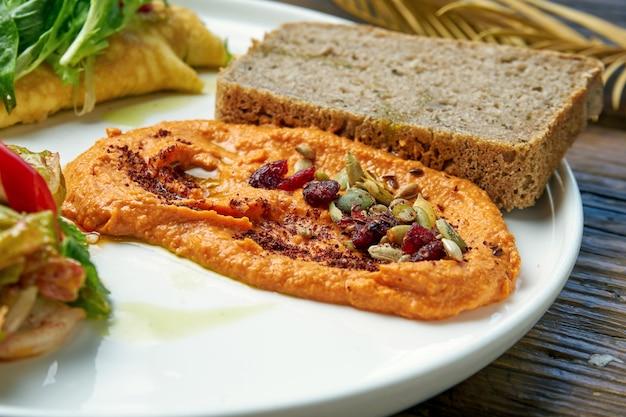 健康的な朝食-木製のプレートでキムチと焼きピーマンフムスのオムレツ