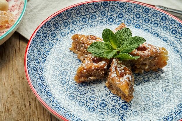 木製の表面にセラミックプレートに蜂蜜とピスタチオと古典的なトルコのバクラヴァ。トルコのペストリーやお菓子。閉じる