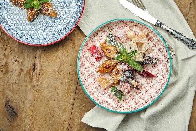 Классическая турецкая пахлава с фисташками и медом в керамической пластине на деревянной поверхности. турецкая выпечка и сладости. закрыть