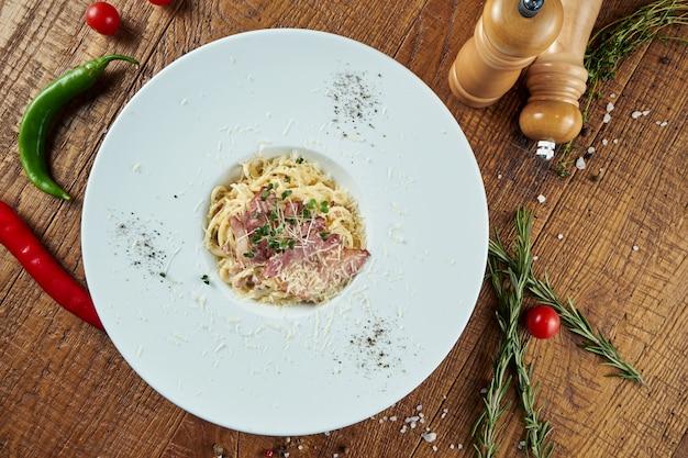 木製のテーブルの白いプレートにベーコンとパルメザンチーズの自家製イタリアンカルボナーラパスタ