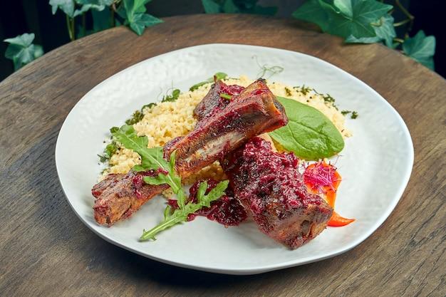 木製の表面の白いプレートにブルガーと食欲をそそる豚カルビのグリル。セレクティブフォーカス。ローストリブ