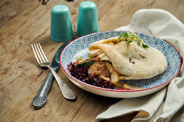 美味しい屋台の食べ物-トマトのピタ、木の表面に青い包丁でキュウリ。ギリシャ料理。ビューを閉じます。シュワルマ