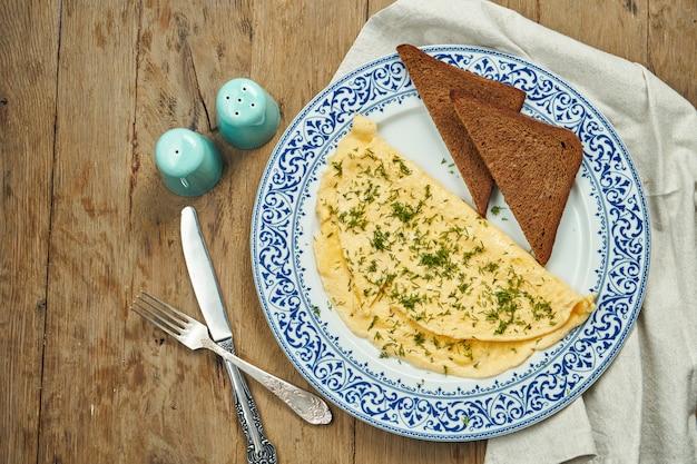 食欲をそそる朝食-木製の表面のセラミックプレートにグリーンとライ麦トーストのオムレツ。