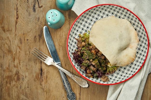 おいしい屋台の食べ物-トマト、きゅうり、木製の表面にブルーベールで牛肉のピタ。ギリシャ料理。ビューを閉じます。シュワルマ