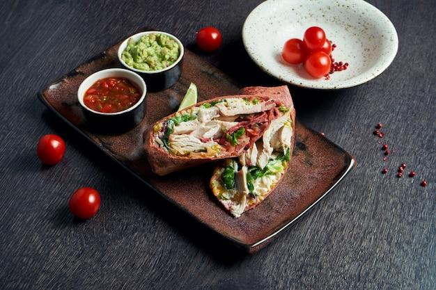 Закройте вверх по взгляду на буррито с цыпленком, рисом, томатами, мозолью и болгарским перцем в коричневом пита на коричневой плите с сальсой томата и гуакамоле. вегетарианский рулет с шаурмой
