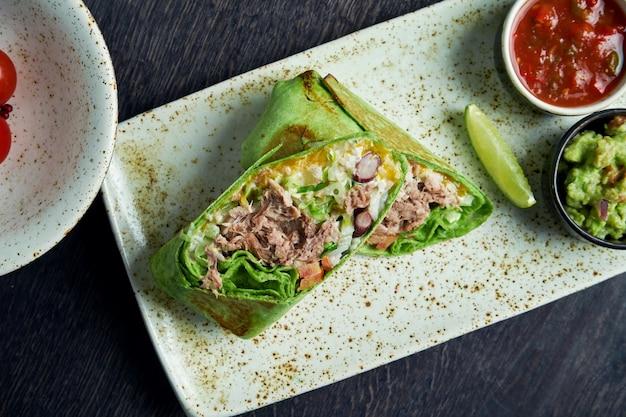 Закройте вверх по взгляду на буррито с говядиной, рисом, томатами, мозолью и болгарским перцем в зеленом пита на коричневой плите с томатной сальсой и гуакамоле. вегетарианский рулет с шаурмой