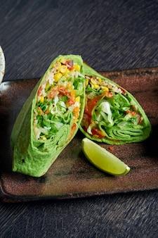 Вегетарианское буррито с рисом, помидорами, кукурузой и болгарским перцем в зеленом лаваше на коричневой тарелке с томатной сальсой и гуакамоле. вегетарианский рулет с шаурмой