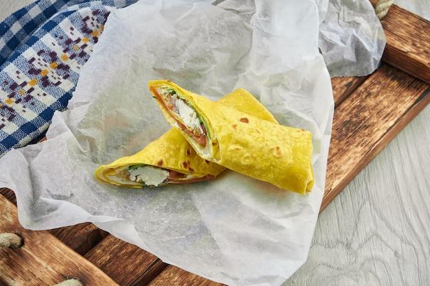 食餌療法のシャワルマは、黄色いピタパンに羊皮紙と木製のトレイをのせて、わずかに塩漬けのサーモンとクリームチーズをロールバックします。クローズアップ、ファーストフード