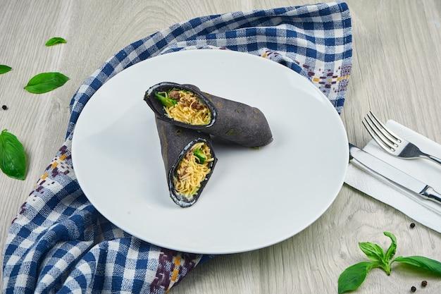 羊皮紙と木製トレイに黒いピタパンにチーズ、マグロ、キュウリと一緒に食事のシャワルマロール。クローズアップ、ファーストフード