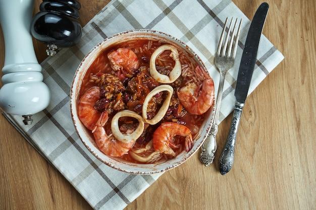 シーフード(エビ、イカ)、豆、ご飯と木製のテーブルの上の白いセラミックボウルで古典的なメキシコのスープ。温かいスープ。平面図、食品フラットレイアウト。ガンボ