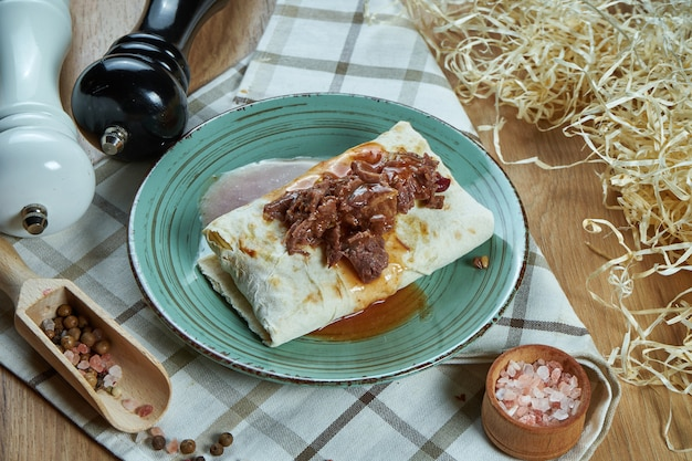 スパイシーな構成で伝統的なゆでた柔らかい牛肉をブループレートにスパイシーなブリトーまたはシャワルマ。ビューを閉じます。食べ物の写真。フラットレイ