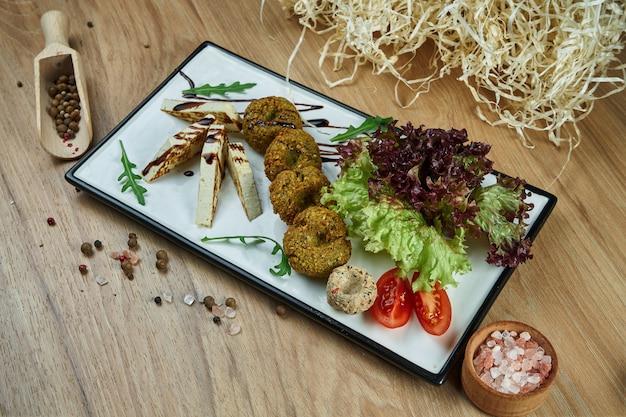 Традиционное блюдо восточной кухни фалафель с хумусом и жареным сыром тофу с гарниром на белой тарелке. продовольственная квартира лежала. вегетарианская еда