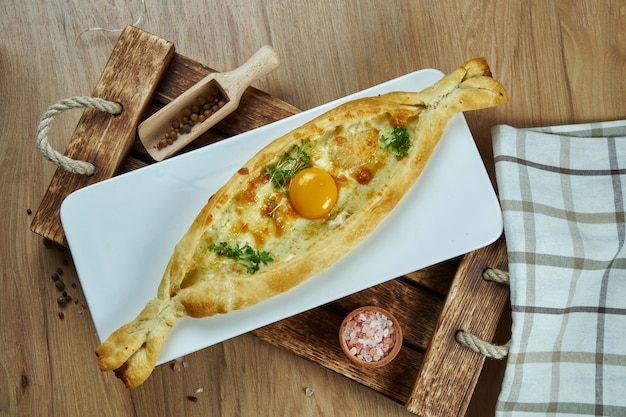 Крупным планом вид на вкусный традиционный аджарский хачапури - открытый запеченный пирог с сыром (сулугуни) и яичным желтком на деревянной доске. традиционная грузинская еда