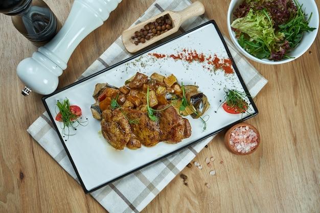 食欲をそそるダイエット料理-焼きチキンまたは七面鳥の切り身と白いセラミックプレートで煮込んだ野菜。上面図。食品フラットレイ