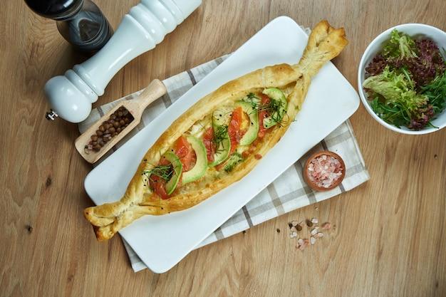 Аппетитный запеченный открытый пирог с соленым сыром сулугуни, лососем и авокадо на белой керамической тарелке. продовольственная квартира лежала.