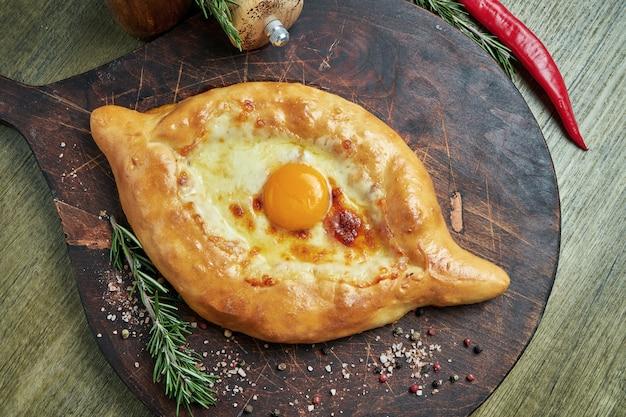美味しい伝統的なアジャリアンハチャプリ-溶かした塩チーズ(スルグニ)と木製のトレイに卵の黄身を開いた焼きたてパイの平面図。伝統的なグルジア料理