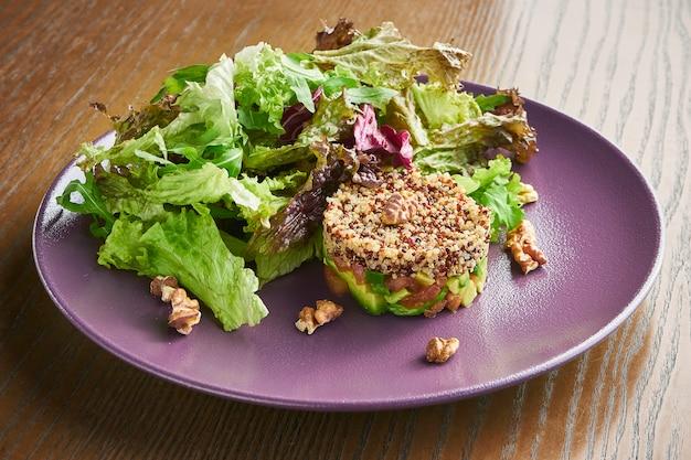 Салат из киноа, авокадо и лосось на фиолетовой тарелке.