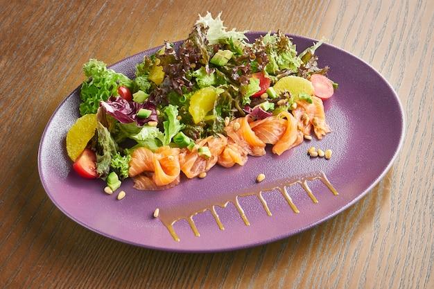Салат с лососем, миксом листьев, помидорами черри на фиолетовой тарелке. полезная и полезная еда.