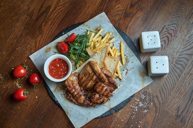 Сочный и необычный израильский стейк из курицы - стейк из бедра без курицы с гарниром из картофеля фри на деревянном подносе. жареная курица. вид сверху еды