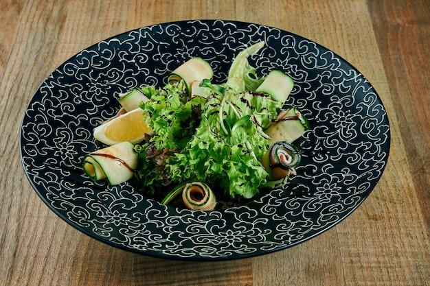 Салат с лососем, миксом листьев, помидорами черри и авокадо в белой миске. полезная и полезная еда.