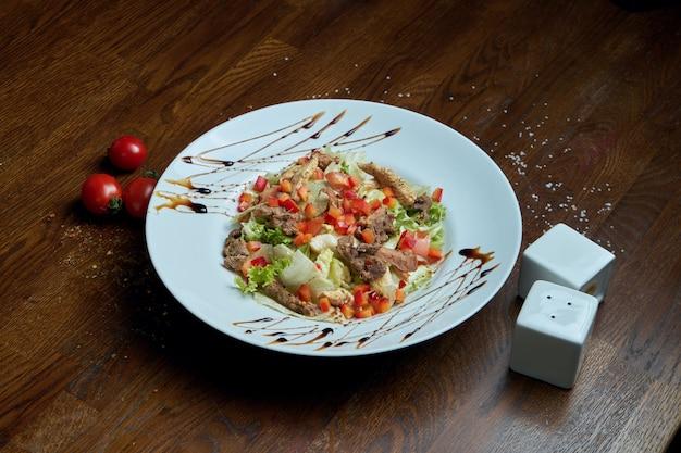 Здоровый теплый салат с жареной говядиной и овощами на белой керамической пластине. композиция с салатом и специями. пищевая фотография