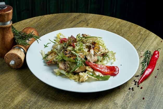 Здоровый теплый салат с жареной индейкой и овощами на белой керамической пластине. композиция с салатом и специями. пищевая фотография