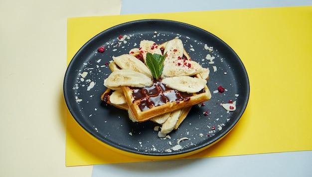 ベルギーワッフル、チョコレート、バナナ、アーモンドを色付きの面の黒い皿に。食欲をそそる甘いペストリー。朝食用食品