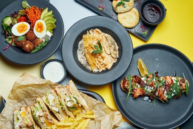 木製のテーブルのさまざまな料理の盛り合わせ。ファラフェルのボウル、サーモンのアボカドトースト、チーズケーキ、サンドイッチ、オートミールとフルーツのダイニングテーブル。トップビュー、食品フラットレイアウト