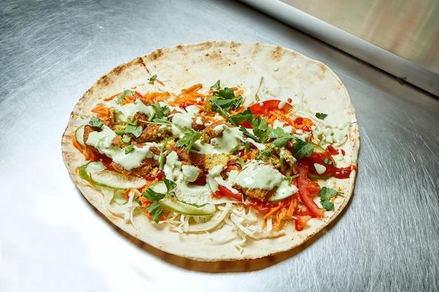金属面にファラフェル野菜、キャベツ、ハーブ、白いピタソースを入れたシャワルマを開きます。おいしい屋台のケバブ