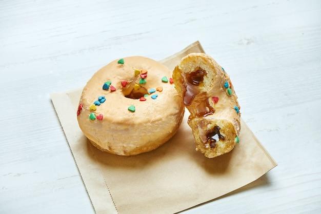 木製のテーブルのクラフトペーパーに黄色のアイシングとキャラメルの詰物で食欲をそそるドーナツ。ドーナツを切る。クラシックなアメリカンデザートペストリー