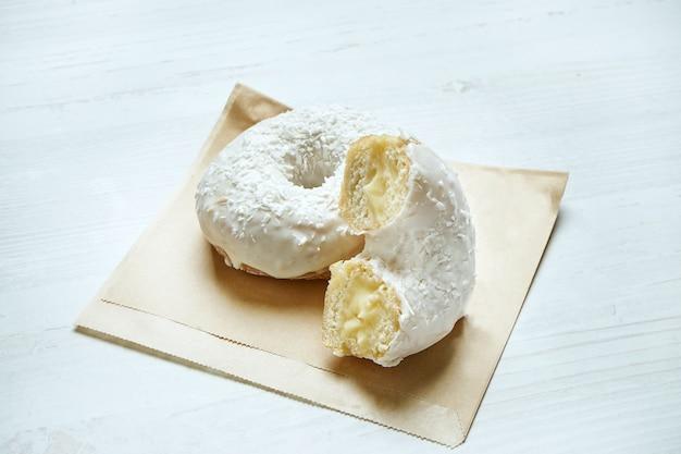 木製のテーブルのペーパークラフトに白いアイシングとココナッツのフィリングで食欲をそそるドーナツ。ドーナツを切る。クラシックなアメリカンデザートペストリー